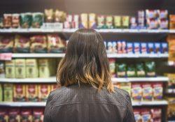 immagine ragazza che guarda scaffale di un supermercato GDO