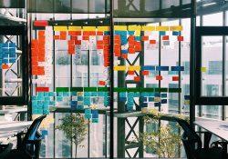 Ufficio smart con pareti a vetro, sedie di design e scrivanie con post it per organizzare lavoro